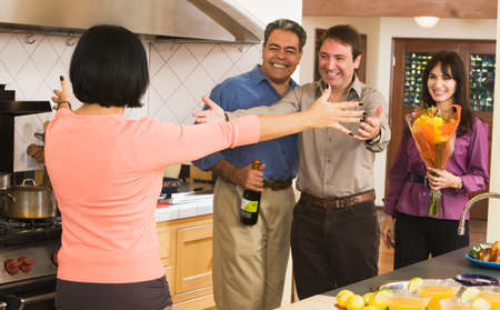 middleaged: Middle-aged friends greeting in kitchen