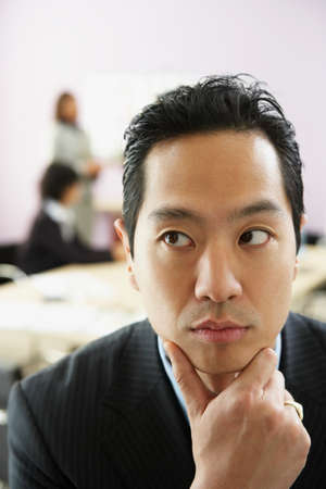 considerate: Asian businessman with chin in hand LANG_EVOIMAGES