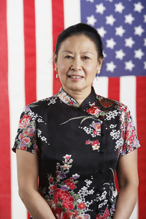 unconcerned: Senior Asian woman standing in front of American flag