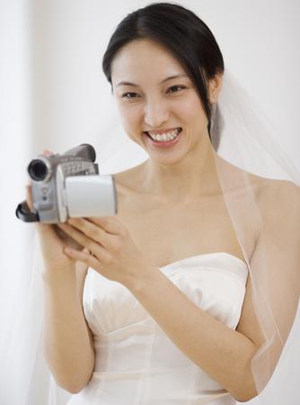 milepost: Asian bride using video camera LANG_EVOIMAGES
