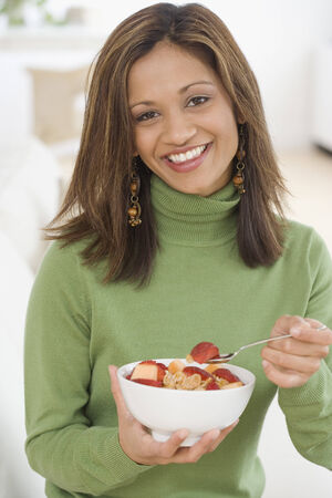Indian woman eating cereal and fruit