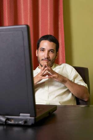 gramma: Hispanic man sitting at desk with laptop LANG_EVOIMAGES