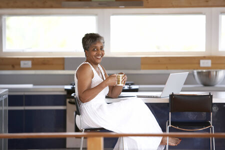 teleworking: Senior African woman drinking coffee