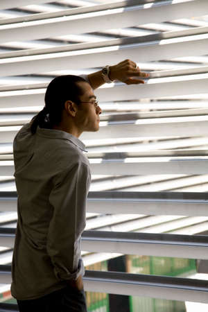 relishing: Hispanic man looking out window