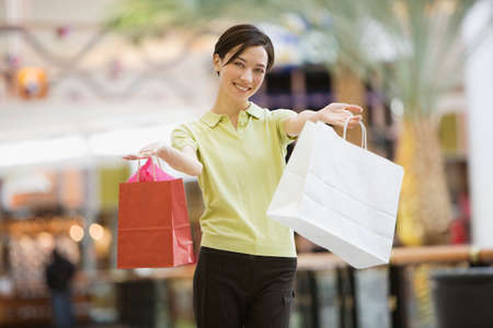go inside: Mixed Race woman holding shopping bags