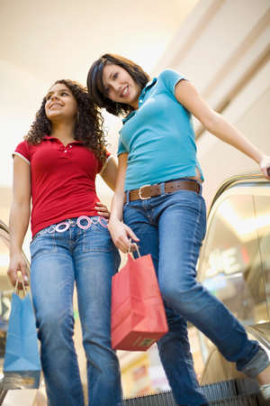 shopping buddies: Multi-ethnic teenage girls riding escalator in mall LANG_EVOIMAGES