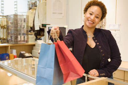 over the counter: Mixed Race woman handing shopping bags over counter LANG_EVOIMAGES