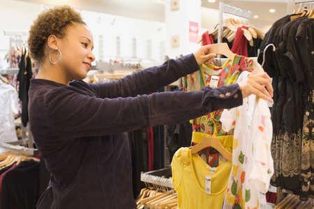 tienda de ropa: Mixed Race mujer de compras en una tienda de ropa