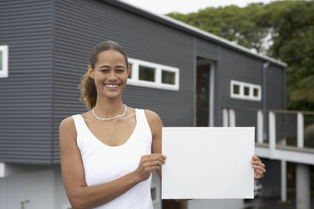 native american ethnicity: Mixed Race woman holding blank paper in front of house