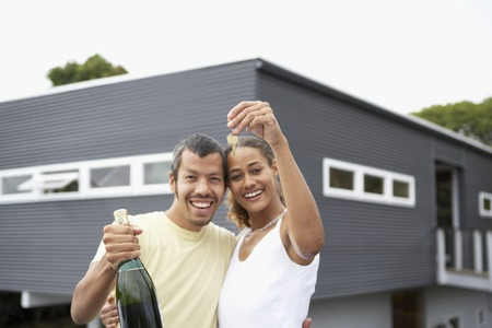Multi-ethnic couple holding keys for new house