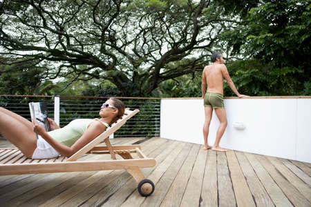 daydreamer: Multi-ethnic couple relaxing on deck LANG_EVOIMAGES