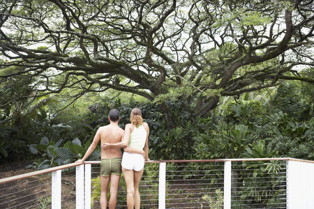 togs: Multi-ethnic couple leaning on railing LANG_EVOIMAGES