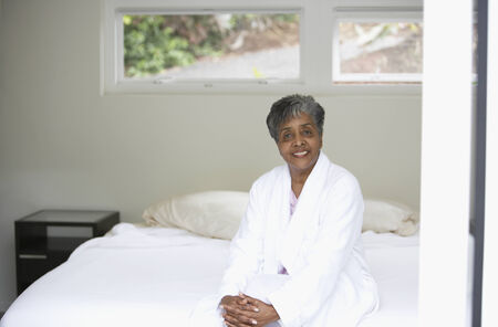 Senior African woman sitting on bed Stock Photo