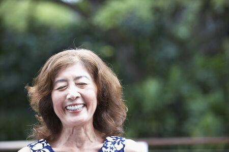 mid life: Senior Asian woman laughing