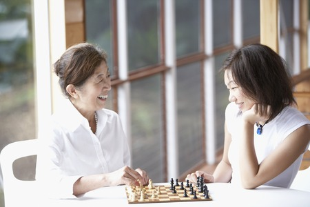 Asian mother and adult daughter playing chess