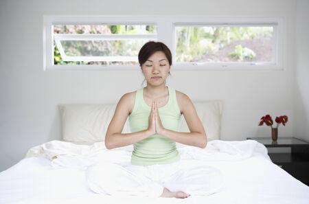 woman meditating: Mujer asi�tica meditando en la cama