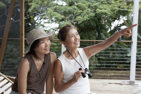 Asian mother and adult daughter pointing and looking 免版税图像