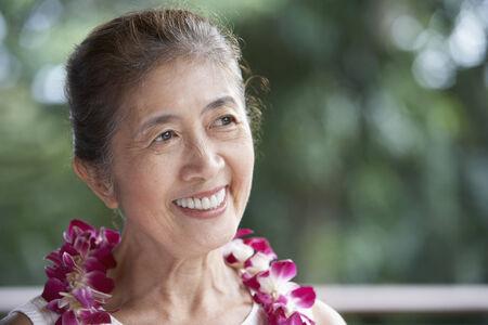Senior Asian woman wearing lei