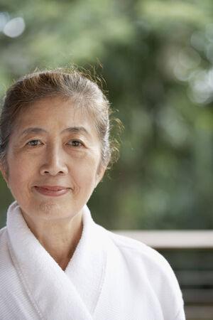 attired: Senior Asian woman wearing bathrobe LANG_EVOIMAGES