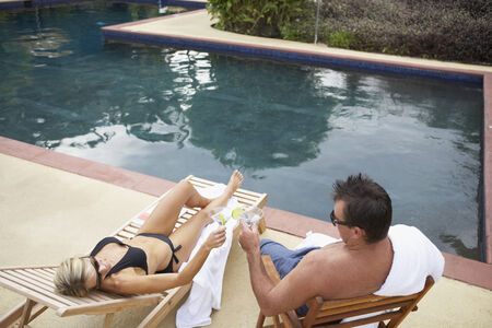 Couple having cocktails next to swimming pool