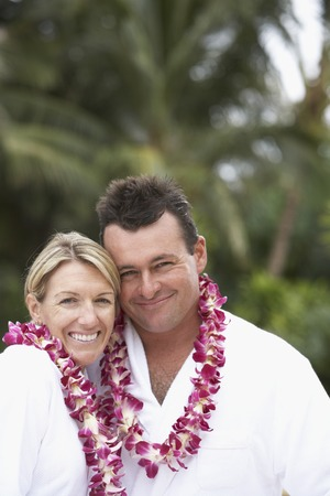 Couple wearing bathrobes and leis LANG_EVOIMAGES