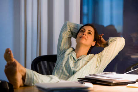 mischievious: Hispanic businesswoman in pajamas at desk LANG_EVOIMAGES