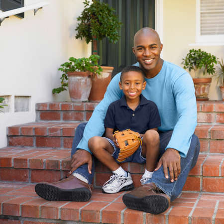 playthings: African American father and son sitting on porch steps