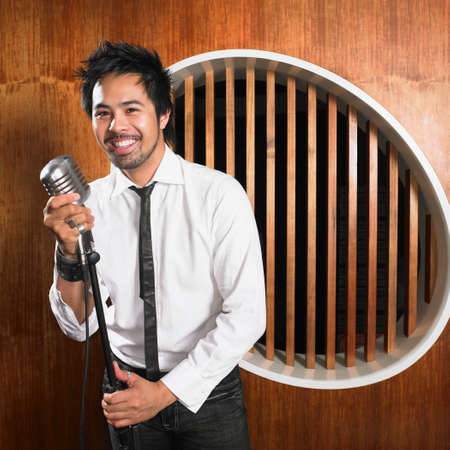 standing: Asian man standing at microphone