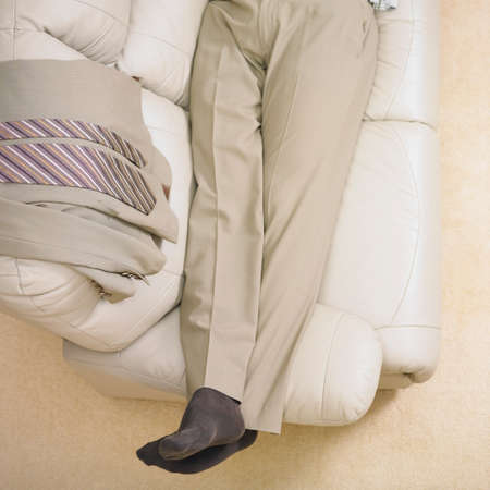 casualness: Businessman laying on sofa