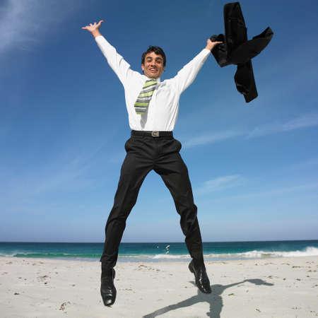 ceasing: Hispanic businessman jumping on beach