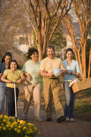 holding family together: Hispanic family walking in park