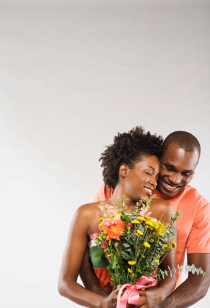 African American couple hugging with flowers