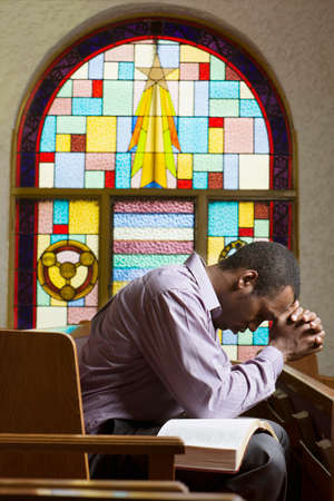 mannen en vrouwen: Afro-Amerikaanse man bidden in de kerk LANG_EVOIMAGES
