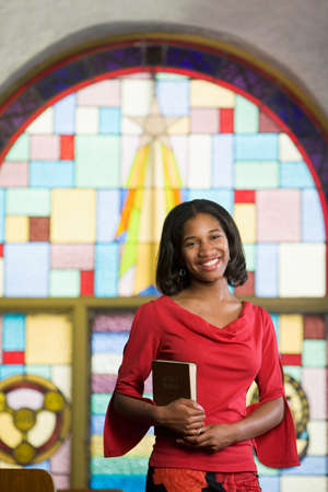 African American Frau mit Bibel in der Kirche LANG_EVOIMAGES