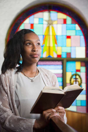 worshipping: African American woman reading Bible in church LANG_EVOIMAGES