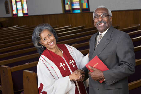 African American female Reverend shaking hands with parishioner Stock Photo