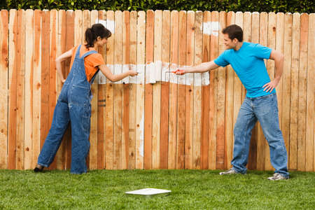 commencing: Multi-ethnic couple painting fence