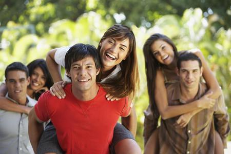 South American men giving girlfriend's piggyback rides Stock Photo
