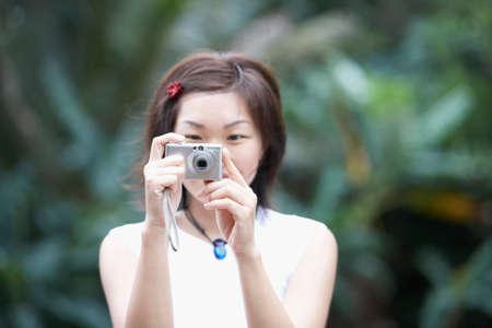 attired: Asian woman taking photograph