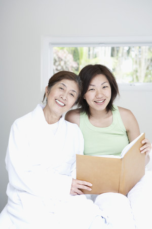 gramma: Asian mother and adult daughter looking at photo album LANG_EVOIMAGES