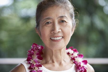 attired: Senior Asian woman wearing lei