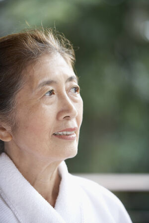 Senior Asian woman wearing bathrobe Stock Photo