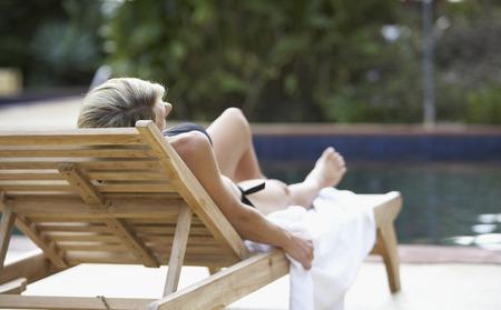 Woman sunbathing next to swimming pool Imagens