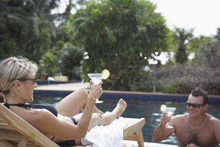 slumbering: Couple having cocktails at swimming pool