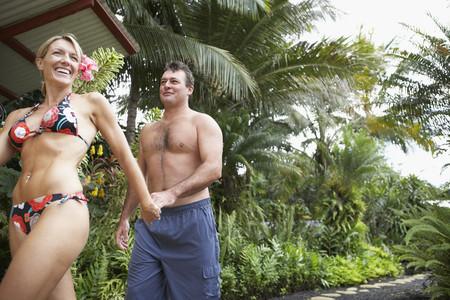 bathingsuit: Couple walking on tropical path