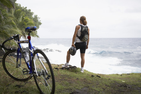 Male cyclist standing on cliff over ocean Banco de Imagens
