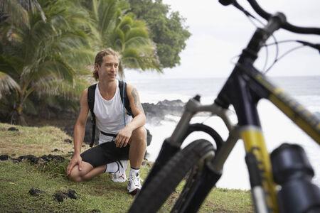 bodyart: Male cyclist on cliff over ocean