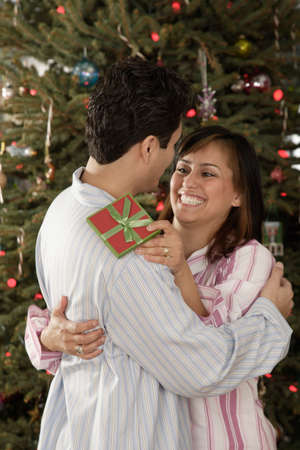 poppa: Hispanic couple hugging on Christmas LANG_EVOIMAGES