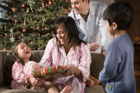 Hispanic family opening gifts on Christmas LANG_EVOIMAGES