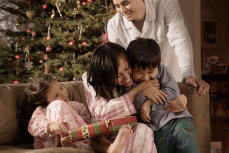 Hispanische Familie umarmt auf Weihnachten LANG_EVOIMAGES